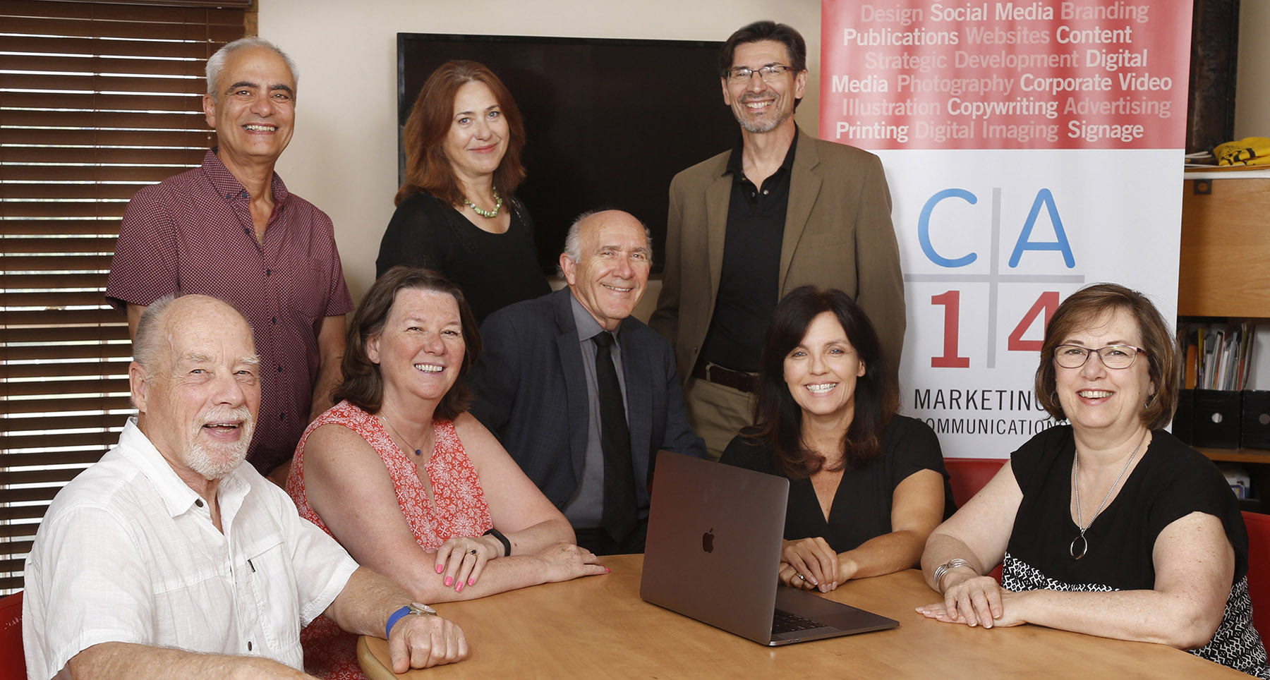 CA14 team sitting at a board table with a screen behind them on the wall and a pull up marketing banner on display.
